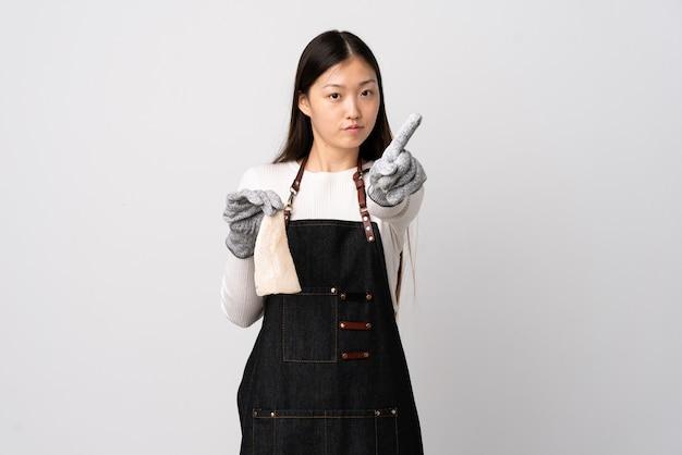 Pescivendolo cinese che indossa un grembiule e che tiene un pesce crudo sopra la parete bianca isolata che mostra e che alza un dito