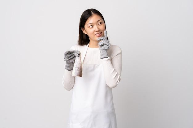 Pescivendolo cinese che indossa un grembiule e che tiene un pesce crudo sopra la parete bianca isolata pensando un'idea mentre osservava