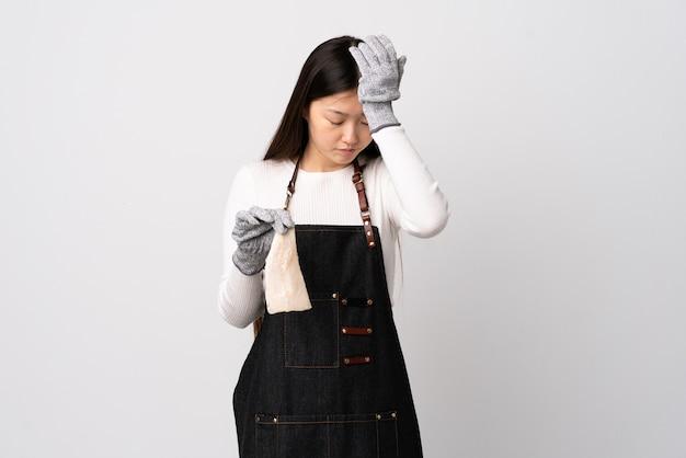 Pescivendolo cinese che indossa un grembiule e che tiene un pesce crudo sopra il muro bianco isolato con mal di testa