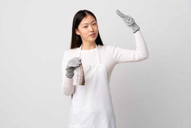 Pescivendolo cinese che indossa un grembiule e che tiene un pesce crudo sopra il muro bianco isolato con espressione stanca e malata