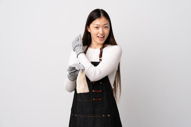 Pescivendolo cinese che indossa un grembiule e che tiene un pesce crudo sopra il muro bianco per celebrare una vittoria