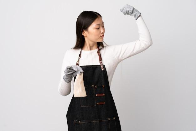 Pescivendolo cinese che indossa un grembiule e che tiene un pesce crudo sopra la parete bianca che fa forte gesto