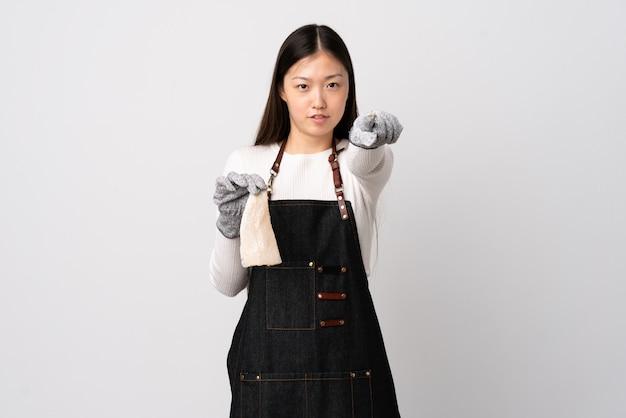 Pescivendolo cinese che indossa un grembiule e che tiene un pesce crudo sopra la parete bianca frustrato e che indica la parte anteriore