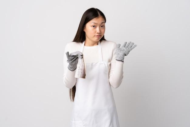 Pescivendolo cinese che indossa un grembiule e che tiene un pesce crudo sopra la parete bianca che ha dubbi mentre solleva le mani