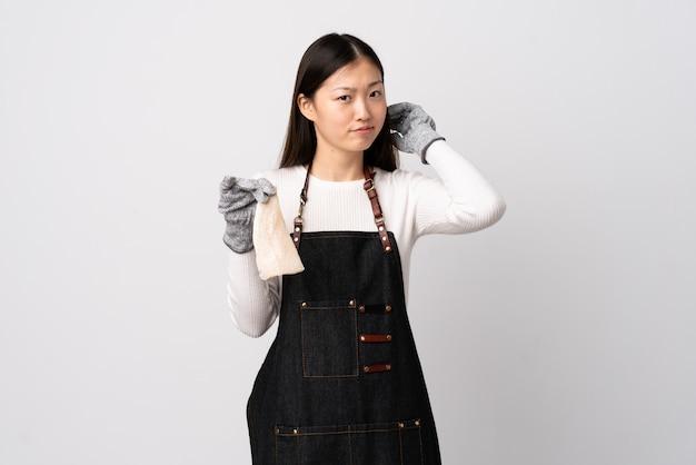 Pescivendolo cinese che indossa un grembiule e che tiene un pesce crudo sopra la parete bianca che ha dubbi