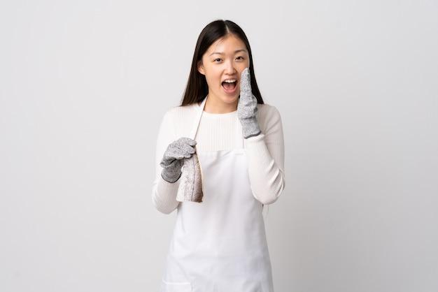 Pescivendolo cinese che indossa un grembiule e che tiene un pesce crudo sopra la parete bianca che grida con la bocca spalancata