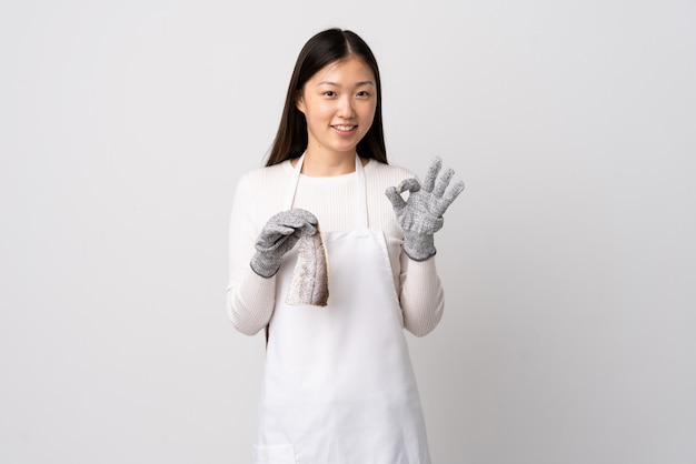 Pescivendolo cinese che indossa un grembiule e che tiene un pesce crudo sopra la parete bianca che mostra segno giusto con due mani