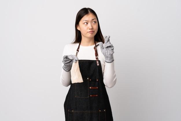 Pescivendolo cinese che indossa un grembiule e che tiene un pesce crudo sopra la parete bianca con le dita che attraversano e che desiderano il meglio