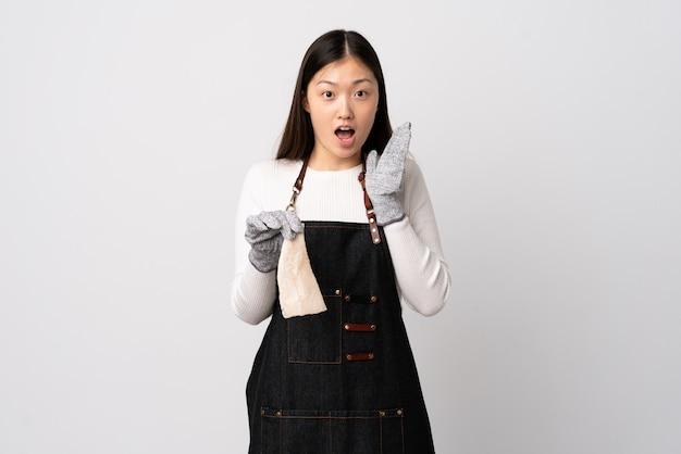 Pescivendolo cinese che indossa un grembiule e che tiene un pesce crudo sopra la parete bianca con espressione facciale sorpresa e colpita