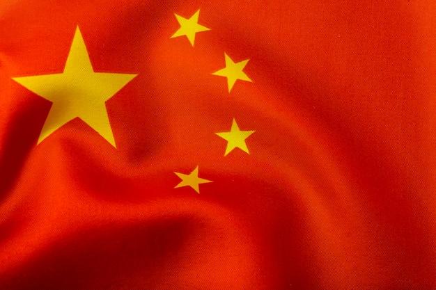 Bandiera cinese. bandiera della repubblica popolare cinese con stelle gialle su sfondo rosso. bandiera cinese con pieghe di seta al vento e trama di tessuti e tessuti