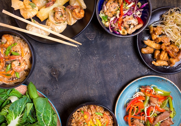 Cibo cinese su sfondo nero. tagliatelle, riso, gnocchi, pollo saltato in padella, dim sum, involtini primavera