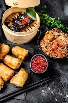 Cibo cinese. tagliatelle, gnocchi, pollo saltato in padella, dim sum, involtini primavera. set di cucina cinese