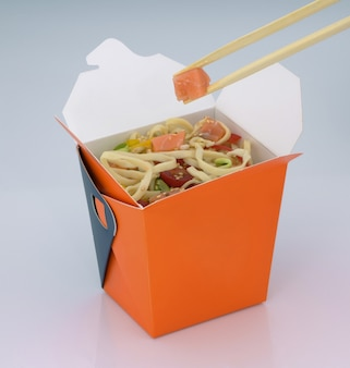 Cibo cinese da asporto noodles con carne e verdure in una scatola di cartone