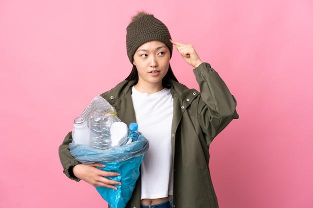 Ragazza cinese che tiene una borsa piena di bottiglie di plastica da riciclare su sfondo rosa isolato avendo dubbi e pensando