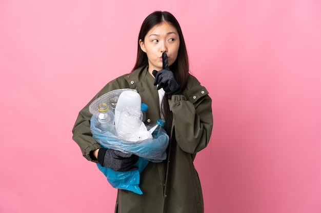 Ragazza cinese che tiene una borsa piena di bottiglie di plastica da riciclare su sfondo rosa isolato che mostra un segno di silenzio gesto mettendo il dito in bocca