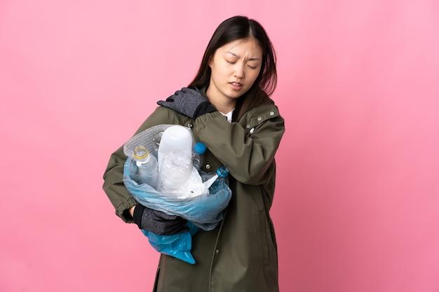 Ragazza cinese che tiene una borsa piena di bottiglie di plastica da riciclare su rosa isolata che soffre di dolore alla spalla per aver fatto uno sforzo