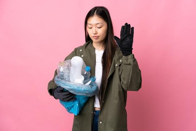Ragazza cinese che tiene una borsa piena di bottiglie di plastica da riciclare sopra la parete rosa isolata che fa gesto di arresto e delusa