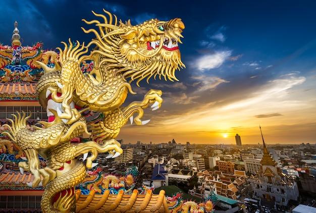 Statua cinese del drago d'oro sul tetto del tempio sullo sfondo del paesaggio urbano e del tramonto