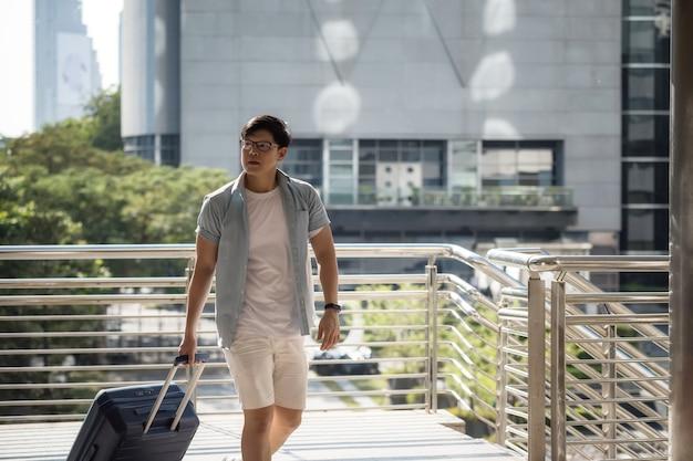 Turista solista cinese o coreano che tira la valigia per viaggiare da solo in città.