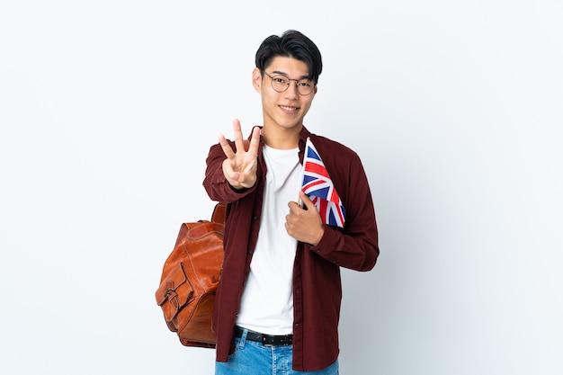 Uomo cinese che tiene una bandiera del regno unito isolata sulla parete viola felice e contando tre con le dita