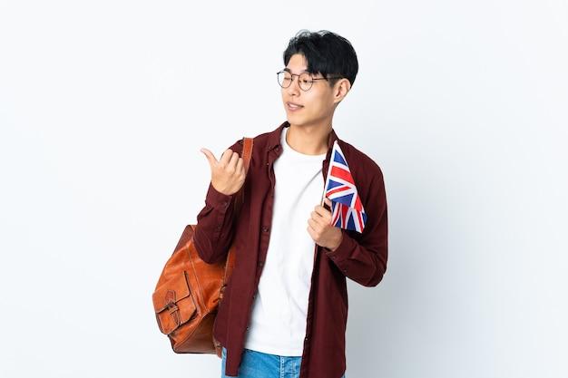 Uomo cinese che tiene una bandiera del regno unito sulla porpora che punta al lato per presentare un prodotto