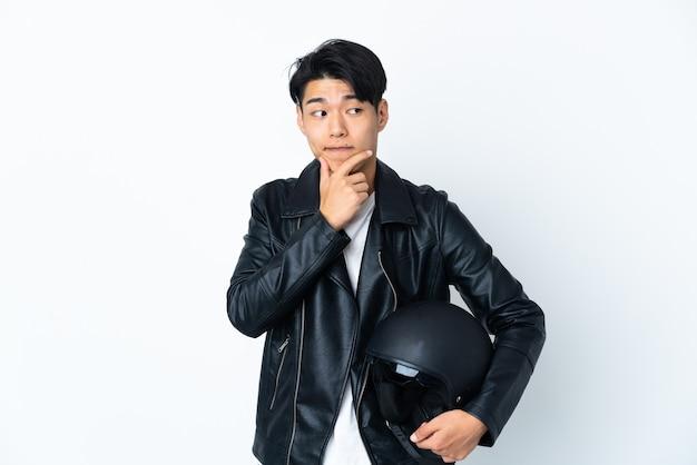 Uomo cinese con un casco da motociclista isolato sul muro bianco avendo dubbi e pensando