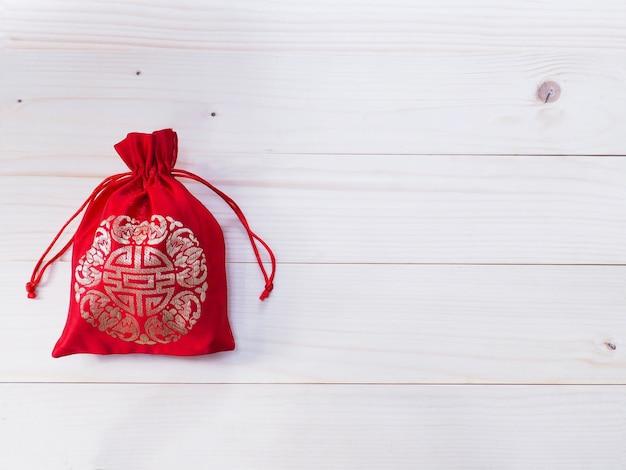 Sfondo di capodanno cinese. sacco di soldi setoso rosso con corda su sfondo di legno di pino naturale e spazio di copia.