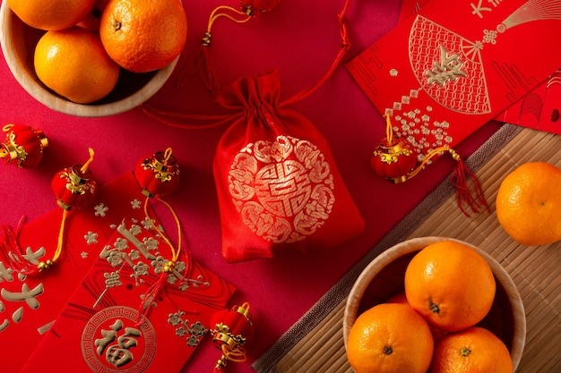 Decorazioni e arance cinesi di festival di nuovo anno su fondo rosso