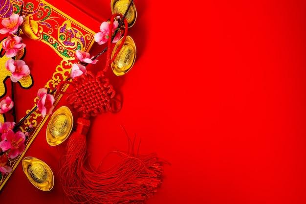 Festa del capodanno cinese con lingotti d'oro su sfondo rosso.
