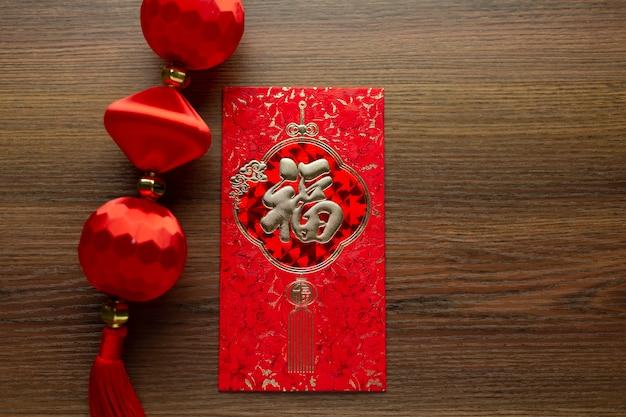 Celebrazioni del capodanno cinese e del capodanno lunare con lingotti d'oro che danno una busta rossa e tè caldo. la parola cinese significa: benedizione, felicità e fortuna