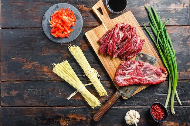 Tagliatelle cinesi con verdure, . bistecca di machete e mannaia da macellaio su sfondo di legno. spazio vista dall'alto per il testo.