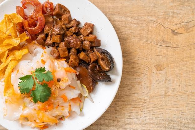 Spaghetti cinesi di riso al vapore con carne di maiale e tofu in salsa di soia dolce. stile di cibo asiatico