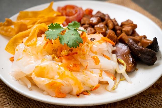 Spaghetti cinesi di riso al vapore con carne di maiale e tofu in salsa di soia dolce - stile di cibo asiatico