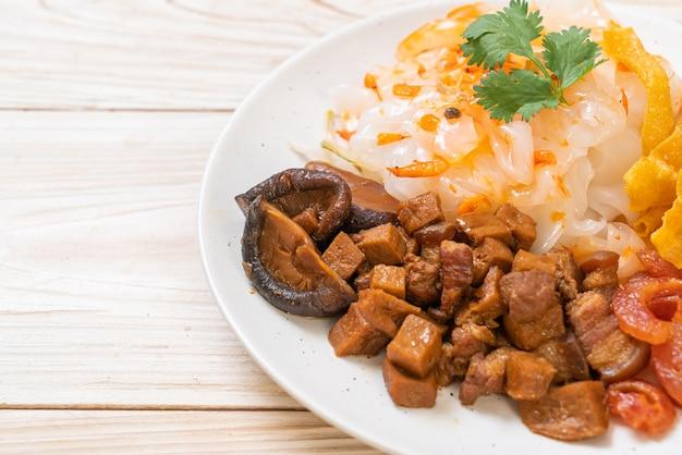 Tagliatelle di riso cinesi al vapore con carne di maiale e tofu in salsa di soia dolce - stile alimentare asiatico