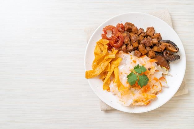 Spaghetti cinesi di riso al vapore con maiale e tofu in salsa di soia dolce