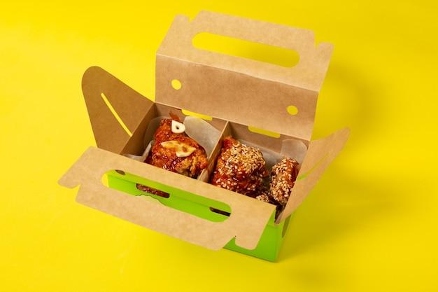 Pollo da asporto cinese con pomodori in una scatola di cartone fotografato su uno sfondo giallo