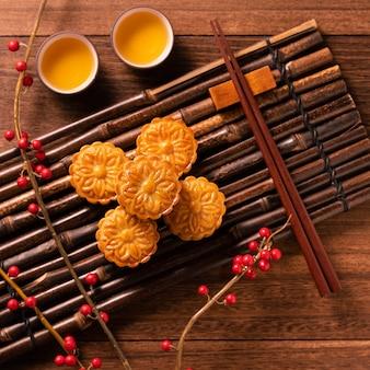 Pasticceria tradizionale cinese mooncake mooncake con tazze da tè su bambù vassoio da portata su sfondo di legno per mid-autumn festival, vista dall'alto, flat lay