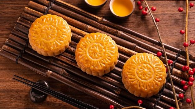 Pasticceria tradizionale cinese mooncake mooncake con tazze da tè su bambù che servevassoio di avvertimento su sfondo di legno per mid-autumn festival, close up