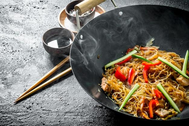 Wok cinese. tagliatelle asiatiche calde di cellophane in un wok della padella sulla tavola di legno scuro