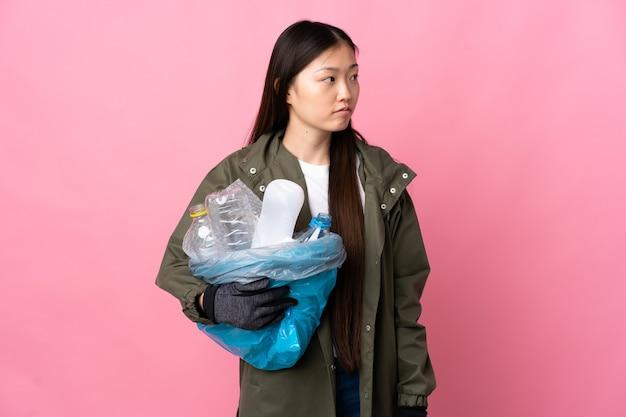 Donna cinese che tiene una borsa piena di bottiglie di plastica da riciclare sul rosa isolato che guarda al lato