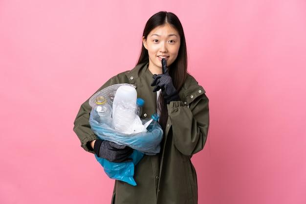 Donna cinese che tiene una borsa piena di bottiglie di plastica per riciclare sopra la parete rosa isolata che mostra un segno di gesto di silenzio che mette il dito in bocca