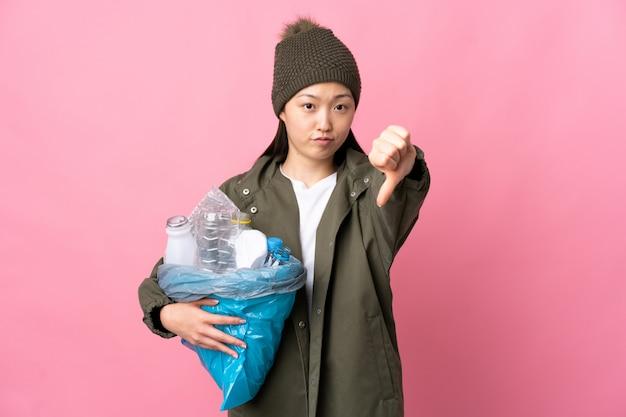 Donna cinese che giudica una borsa piena delle bottiglie di plastica per riciclare sopra la parete rosa isolata che mostra pollice giù con l'espressione negativa