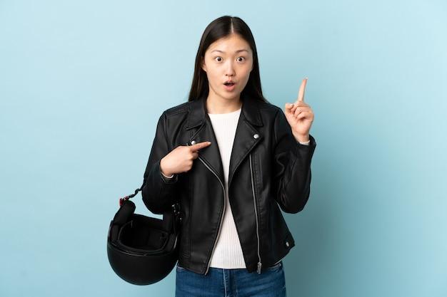 Donna cinese che tiene un casco del motociclo sopra la parete blu isolata con l'espressione facciale di sorpresa