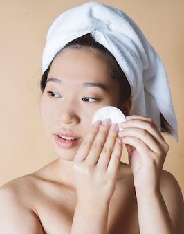 La donna cinese esegue la pulizia del viso con il cetriolo su sfondo giallo