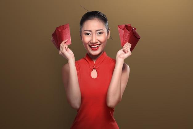 Donna cinese in abbigliamento tradizionale che tiene angpao