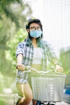 Giovane donna cinese in casco e mascherina medica che guida sulla bicicletta in città