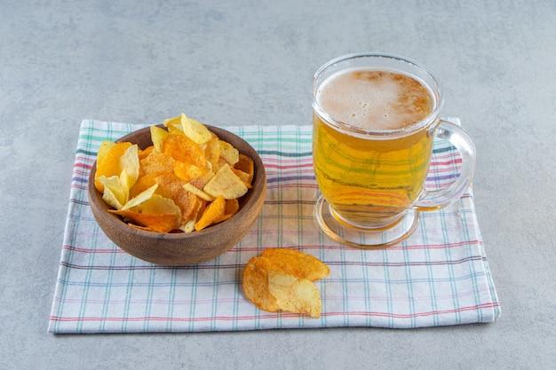 Patatine in una ciotola accanto a un bicchiere di birra su uno strofinaccio, sulla superficie del marmo.