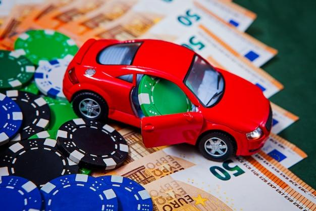 Chip, soldi, euro su un tavolo da poker verde con una macchina da scrivere audi in rosso