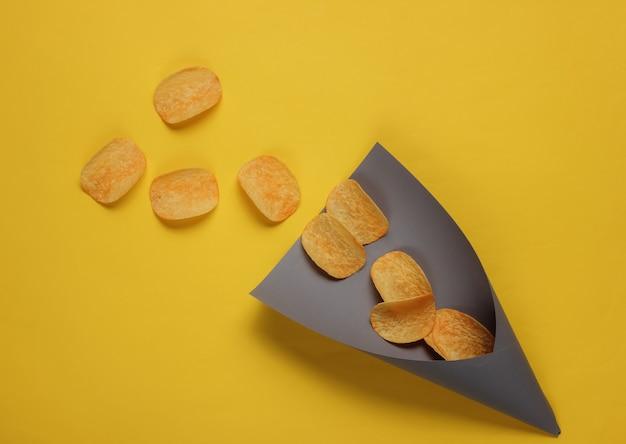 Fette di patatine fritte in sacchetto di carta su colore giallo