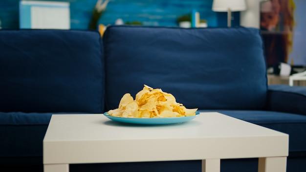 Spuntino con patatine seduto sul tavolino da caffè davanti a un comodo divano nel soggiorno moderno senza nessuno, mobili e pareti blu, splendidamente decorati. arredamento abbastanza semplice dell'appartamento, decorazione elegante.